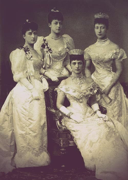 Princess Alexandra of Wales and her three daughters at her son's wedding in 1893. Alexandra and her married daughter, Louise, are both wearing diamond tiaras and off-the-shoulder formal gowns. Her two unmarried daughters, Victoria and Maud, are wearing formal gowns with puffed sleeves.