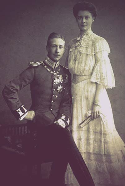 Cecile of Mecklenburg-Schwerin and Crown Prince Wilhelm of Prussia and Germany. Wilhelm is sitting down with a stern look on his face, while Cecilie stands tall beside him with a gentle smile on her face.