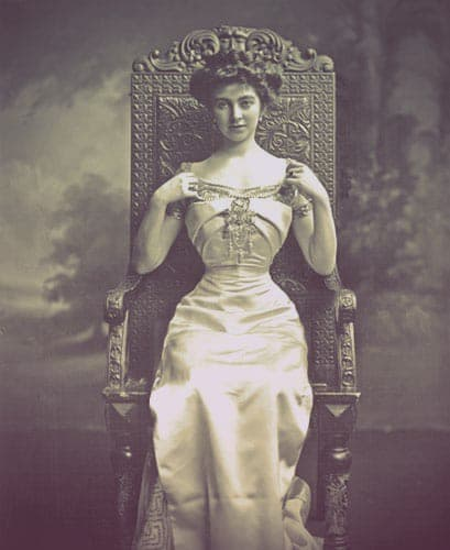 Constance Edwina Cornwallis-West, wife of the second Duke of Westminster. The image shows a young woman in satin evening gown seated in an ornate chair. She is wearing a corset to achieve the wasp-waisted look popular in Edwardian fashion.