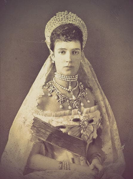 Empress Maria Feodorovna of Russia. The image shows a young, beautiful woman with short, dark hair wearing a diamond kokoshnik tiara, multiple rows of pearl and diamond necklaces, and an off-the-shoulder Russian court gown.