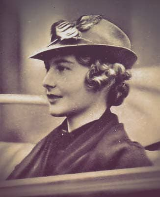 Princess Cecilie Viktoria of Prussia seated in a car. She's wearing a stylish hat pointed in front, over short curled hair.