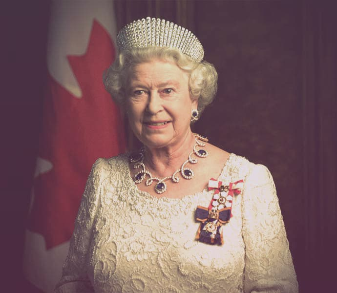 Queen Elizabeth II standing in front of a Canadian flag. She is wearing the diamond kokoshnik tiara, a sapphire and diamond necklace, and a white gown.