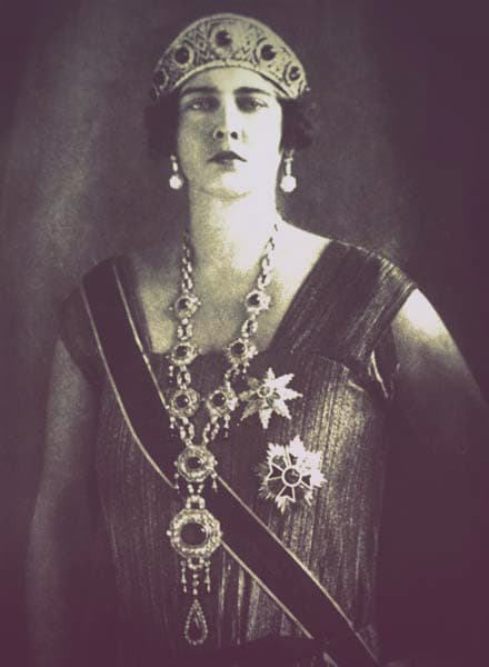 Queen Maria of Yugoslavia wearing the emerald kokoshnik. She is wearing a sleeveless flapper-style dress with large earrings, an enormous jeweled pendant necklace, and two orders pinned to her chest.