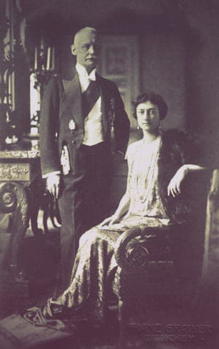 Crown Prince Rupprecht of Bavaria with his wife, the former Princess Antonia of Luxembourg. Both are in evening dress. Rupprecht stands beside Antonia, who is seated in a chair.