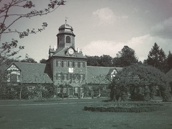 Schloss Wolfsgarten, the Hesse family's hunting lodge with a brick face, domed central tower, and lush green lawn.
