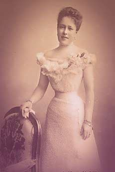 Archduchess Maria Christina of Austria. She's wearing an off-the shoulder pale ballgown with a tightly corseted waist. Her hair is up, and she's wearing small drop earrings, a choker, a floral corsage on her dress, and bracelets on both wrists.  | From Archduchess Maria Anna of Austria's Tiara on GirlInTheTiara.com.