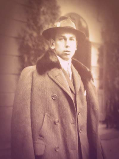 A young Archduke Albrecht, dressed in an overcoat, fedora, and suit. He's staring at the camera with an expressionless face.  | From Archduchess Maria Anna of Austria's Tiara on GirlInTheTiara.com.