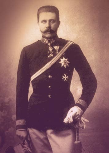 Archduke Franz Ferdinand wearing a military uniform. He has several medals pinned to his uniform, and a gold braided cord across his chest. He has short, stiff, dark hair and a fancy curling mustache. | From Archduchess Maria Anna of Austria's Tiara on GirlInTheTiara.com.
