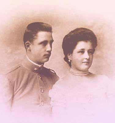 Maria Anna and Elias together. He's wearing a simple military uniform and she's wearing a high-necked white dress and a simple pair of pearl earrings.  | From Archduchess Maria Anna of Austria's Tiara on GirlInTheTiara.com.