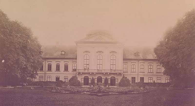 Grassalkovich Palace in Bratislava (then called Pressburg). A triangular cornice tops the front of the palace, with two long arcades of rooms extending in either direction. Lush green trees and gardens frame the palace. | From Archduchess Maria Anna of Austria's Tiara on GirlInTheTiara.com.