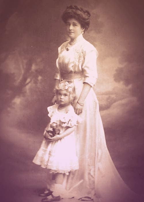 Maria Anna standing with her daughter Elisabetta. She's wearing a high-necked white dress with a long pearl necklace and a sapphire brooch. Also, her hair is piled on her head and wound around in a braid. It's impossibly thick and lush. Little Elisabetta is blonde, wearing a short white dress with adorable white ankle socks and black buckle shoes. | From Archduchess Maria Anna of Austria's Tiara on GirlInTheTiara.com.