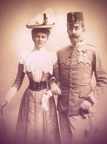 Sophie Chotek and Franz Ferdinand, standing arm-in-arm. She's wearing a day dress and a hat and carrying a walking stick. He's dressed in a military uniform complete with tall hat, sword at his side. | From Archduchess Maria Anna of Austria's Tiara on GirlInTheTiara.com.