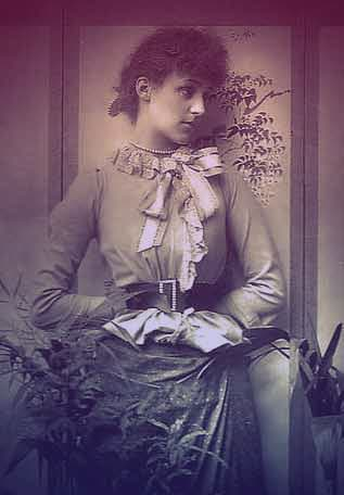 Violet Manners, Duchess of Rutland, seated in a chair. She's looking off to the left, wearing an informal high-necked long-sleeved blouse, belt with diamond buckle, and skirt. Her waist is tightly corseted. | The Secret Rooms by Catherine Bailey book review
