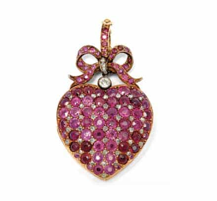 A heart-shaped locket covered with rubies and a ruby-encrusted bow on top.