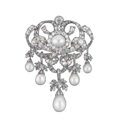 An ornate devant-de-corsage brooch in a garland style with a center pearl, diamond surround, and five additional drop pearls.