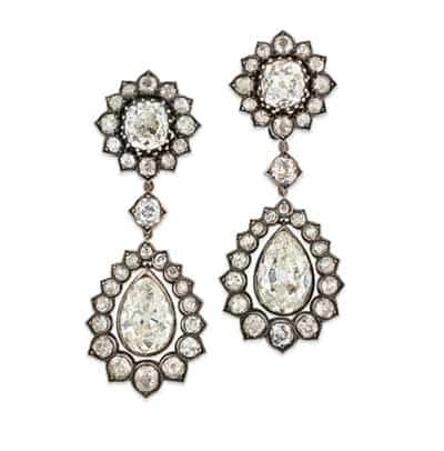 Diamond drop earrings. The top diamonds and pear-shaped bottom diamonds are both framed by surrounding smaller diamonds.