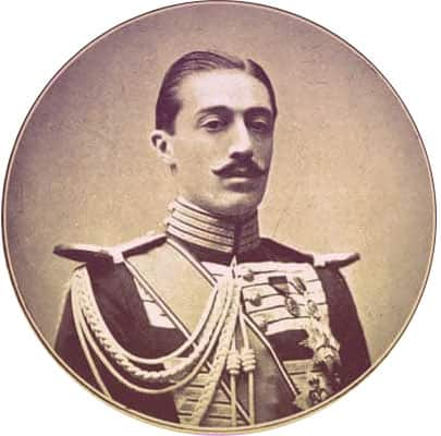 A round portrait of the Duke. He has short, slicked-back dark hair, dark eyebrows, and an artfully curled black mustache. He's wearing a military uniform with a gold collar, gold braid, gold sash across the chest, and multiple medals pinned to his chest. | From The Yusupov Black Pearl Necklace on GirlInTheTiara.com.