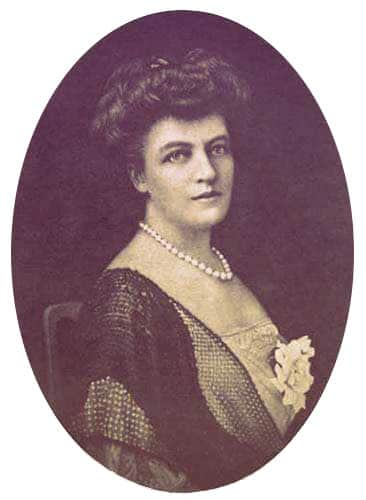 A photo of Eleanor Widener, wearing a day dress with a single strand of pearls and a flower pinned to her chest. | From The Yusupov Black Pearl Necklace on GirlInTheTiara.com.