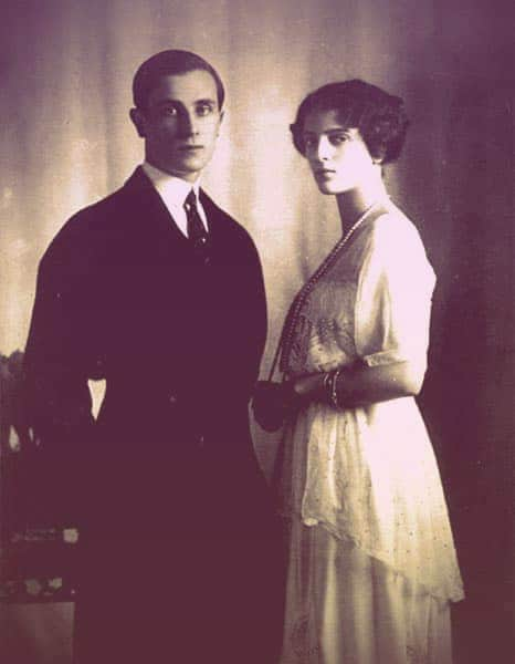 An engagement photo of Felix and Irina, taken in 1913. He's clean-cut, dressed in a dark suit, standing with his hands folded behind his back. Irina stands next to him but not touching him, dressed in a pretty, lacy white day dress with one long strand of pearls.  | From The Yusupov Black Pearl Necklace on GirlInTheTiara.com.