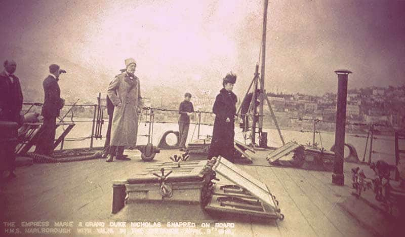 A photo taken on the deck of the Marlborough, showing Maria Feodorovna standing along, dressed in a long black coat and black hat. A couple men in suits are standing against the rail behind her, one using binoculars to look back at short. A man in a gray military coat and Astrakhan hat stands behind Maria. | From The Yusupov Black Pearl Necklace on GirlInTheTiara.com.