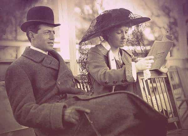 Mathilde and Peter on a bench at the horse track. Peter is dressed in an overcoat and bowler hat, looking intently at the race. Mathilde is wearing a big hat with a lace veil and is looking at the program. | From The Yusupov Black Pearl Necklace on GirlInTheTiara.com.