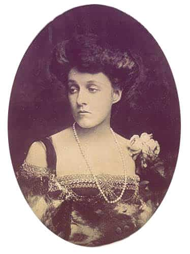 A photo of Mathilde from 1910. Her hair looks much darker than the usual blonde, but it's still piled on her head in a Gibson Girl pompadour bun. She's wearing an evening dress with cutouts over the shoulders and a long string of pearls. | From The Yusupov Black Pearl Necklace on GirlInTheTiara.com.