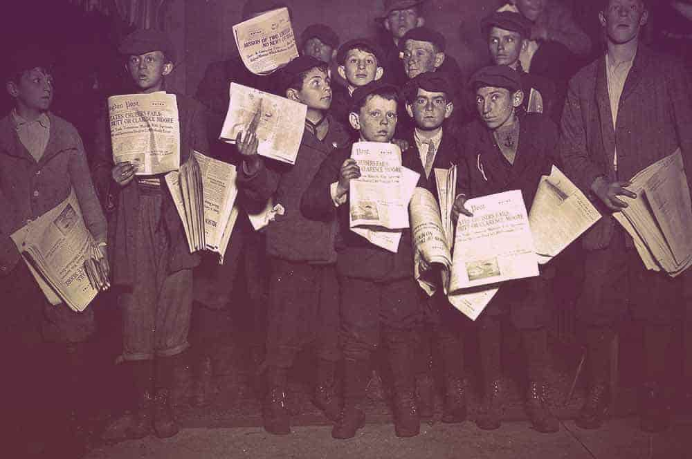 A dozen newsboys standing holding their newspaper up for the camera. They're dressed in black knickers, jackets, and collared shirts.  | From The Yusupov Black Pearl Necklace on GirlInTheTiara.com.