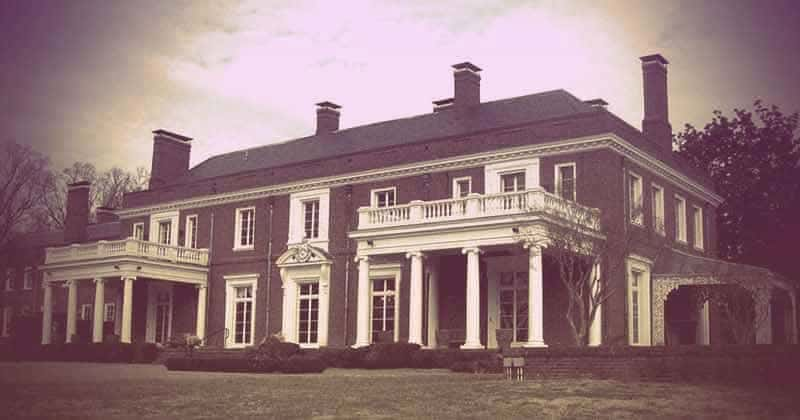 A two-story colonial-style mansion with two second-story decks supported by columns. The house is brick with white window frames and detailing. | From The Yusupov Black Pearl Necklace on GirlInTheTiara.com.
