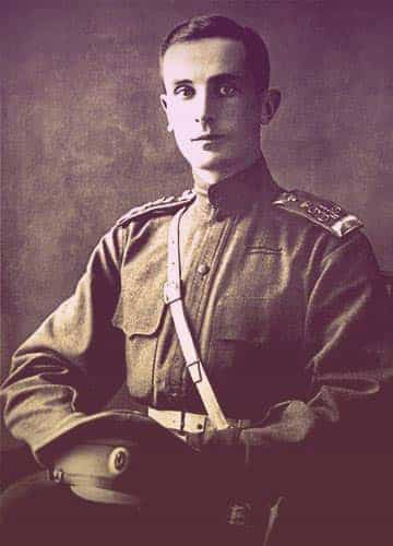 A photo of Felix, seated, dressed in a very simple military uniform - no epaulets, no medals, no sashes. He has short, dark, neatly trimmed hair and has a faint smile as he looks at the camera. | From The Yusupov Black Pearl Necklace on GirlInTheTiara.com.