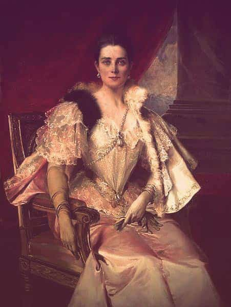 A portrait of Zinaida Yusupova. She's sitting in a chair with a draped red background behind her. She's wearing a cape over one shoulder, black pearl drop earrings, and a huge pearl attached to a diamond chain draped across her chest. Her blouse is lacy, trimmed with fur t the shoulders and pointed in a deep V. Her skirt is pale pink. | From The Yusupov Black Pearl Necklace on GirlInTheTiara.com.