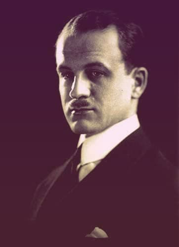 A photo of Sumner Welles. He's dressed in a dark suit with a light-colored pocket square. His dark hair is receding at the temples slightly. He has a small, dark mustache. | From The Yusupov Black Pearl Necklace on GirlInTheTiara.com.