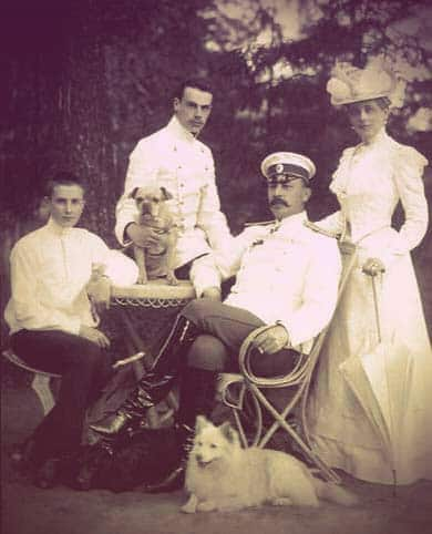 Photo of Zinaida and her family. She's on the right, dressed in a high-necked white day dress with a big white hat and parasol. Felix Sr. is seated with a white dog at his feet. He's wearing a military uniform and shiny black books. Nicholas is behind his father, holding another small dog. He has deep-set eyes and a thin, dark mustache. Felix is seated on the left. He's a teenager with a buzz cut, dressed in a simple white tunic and black pants. | From The Yusupov Black Pearl Necklace on GirlInTheTiara.com.