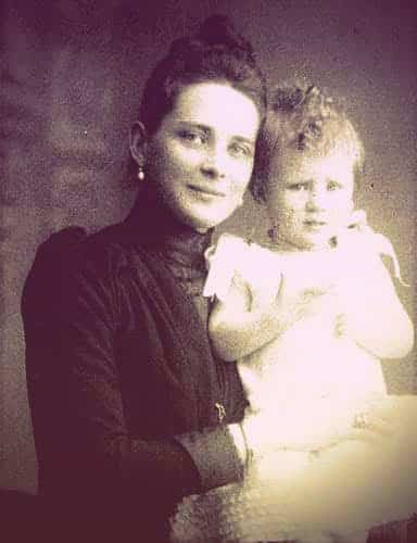 A photo of Zinaida holding one of her sons, who looks about a year old. Zinaida is wearing pearl drop earrings and a black day dress with long sleeves and a high neck. The baby has messy, curly blond hair. | From The Yusupov Black Pearl Necklace on GirlInTheTiara.com.