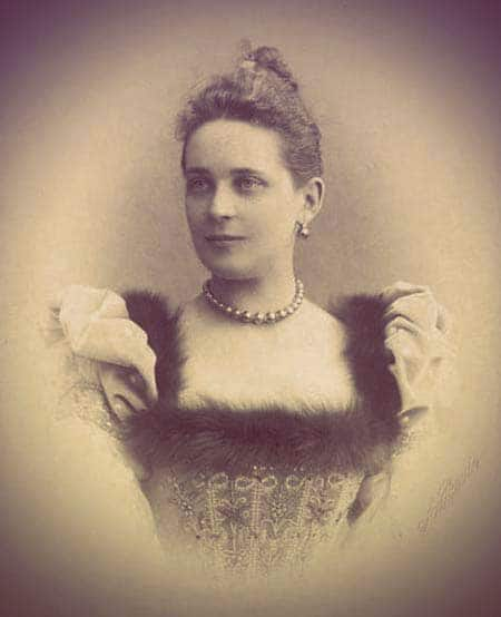 A photo of Zinaida wearing a square-necked dress trimmed with fur. Her hair is slightly wavy and pulled back in a bun. She's wearing black pearl drop earrings and the black pearl necklace. The necklace fits snugly around the base of her neck - while in the photo of Mathilde, the necklace hangs down a bit lower. | From The Yusupov Black Pearl Necklace on GirlInTheTiara.com.
