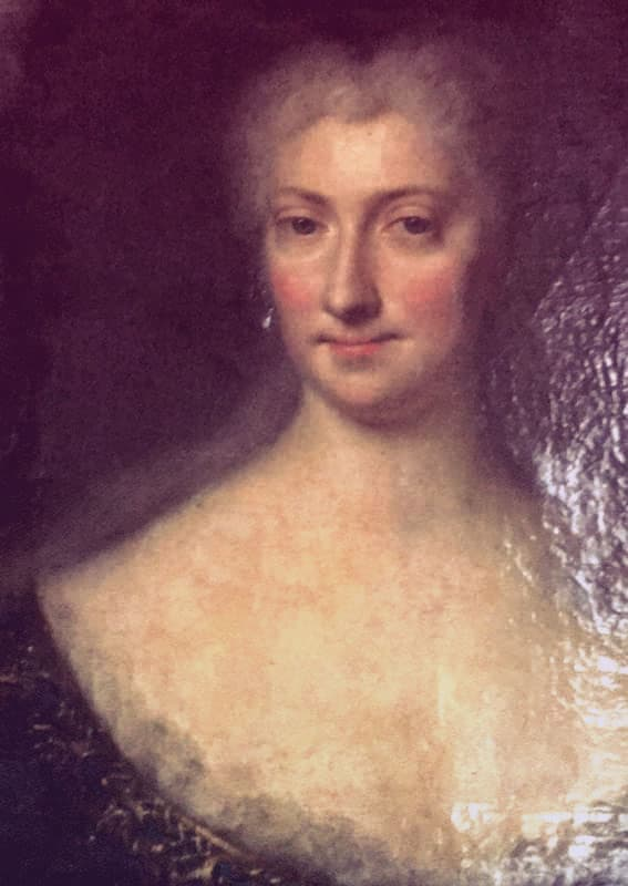 This portrait is most likely Eleonora von Schwarzenberg. The sitter is a handsome, mature woman with a long white powdered wig on. She's looking directly at the viewer. She has drop pearl earrings, and is wearing a low, scoop-necked dress with a chemise peeking up over the neckline. It's a very serene, majestic portrait.