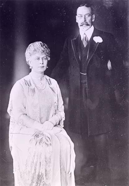 King George V in a dark suit and Queen Mary in a pale day dress with a pearl necklace and earrings.
