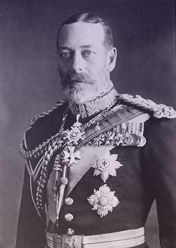 King George V wearing a military uniform with braided shoulder boards, medals, orders, and a sash across his chest.