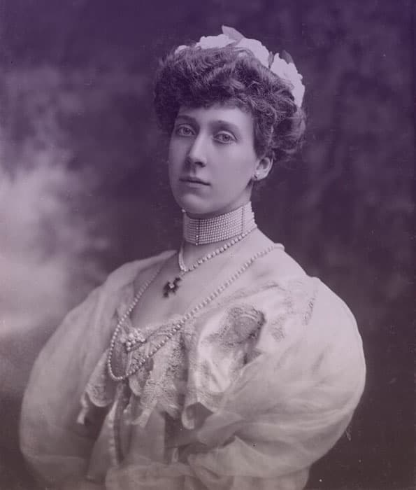 Princess Louise of Schleswig-Holstein in an evening gown with a pearl dog collar, cross necklace, and longer strand of pearls.