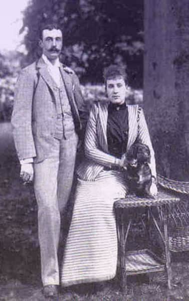 Louise and Aribert with a small black dog. She's wearing a striped skirt suit.