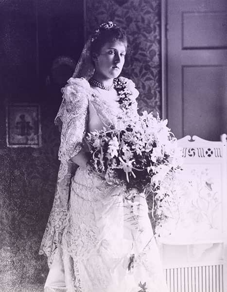 Louise in her wedding dress and veil, holding a large bouquet.