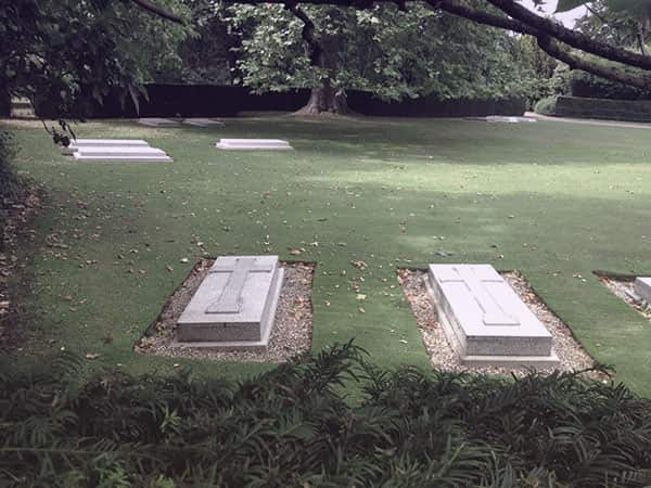 Two raised graves in a grassy park. They are seemingly identical with crosses on top.