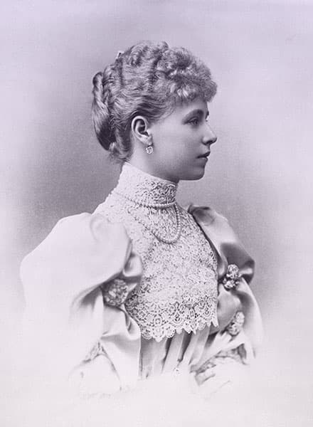 Marie of Romania wearing a high-necked lacy day dress with a pearl  necklace.