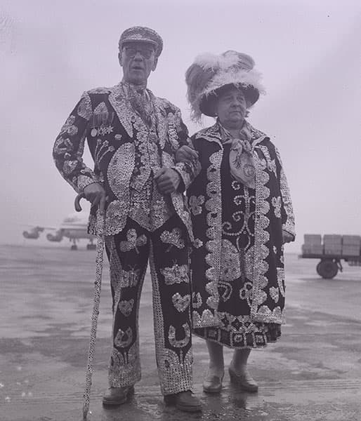 A man and women, both wearing black outfits decorated with thousands of mother-of-pearl buttons sewn on in elaborate decorative patterns.