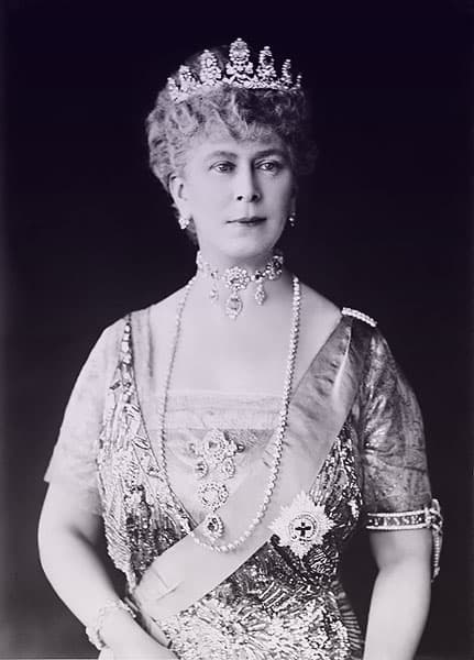 Queen Mary in a sparkling evening gown with her garter armband, sash, and a parure of sapphire and diamond jewels.