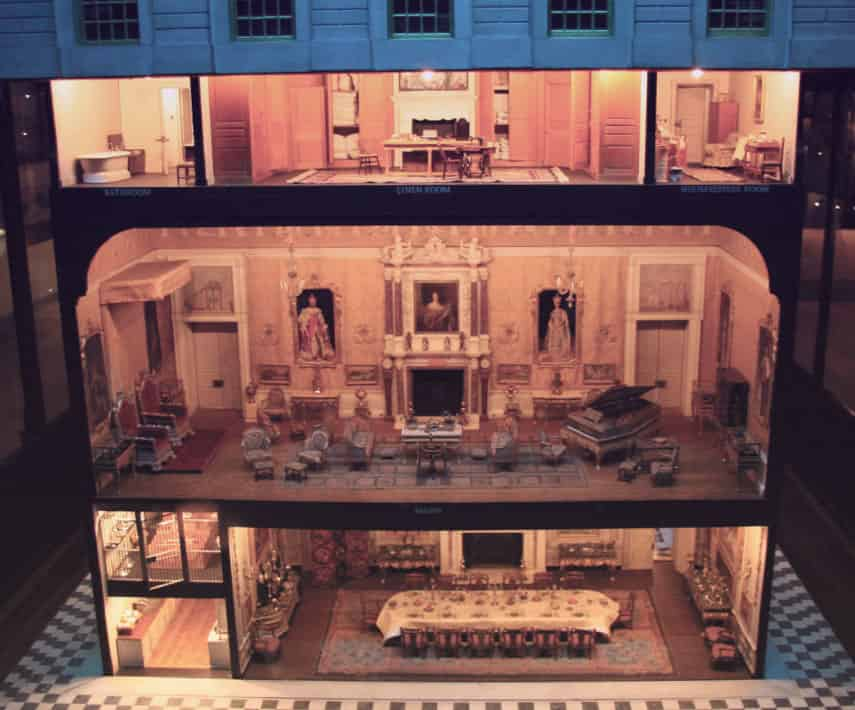 Three stories of a doll house, showing a dining room, salon with a piano and formal portraits, and bedrooms and bathrooms.