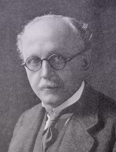 Edwin Lutyens wearing a dark three-piece suit and small, dark, glasses with circular lenses.
