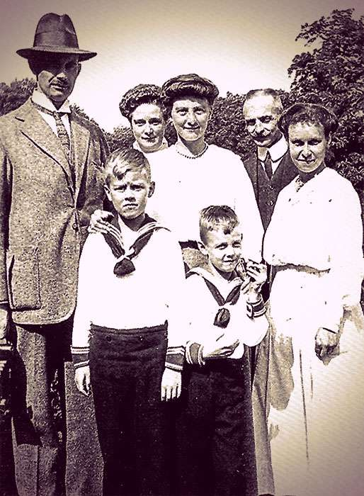 Alexandra of Mecklenburg-Schwerin and her family and household members standing in front of tall trees. The two boys are wearing sailor suits.