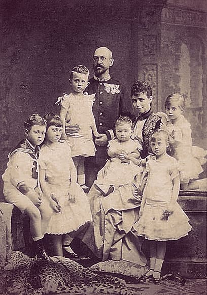 Family portrait with Ernst August, Thyra, and their 6 kids. Alix is standing on the right, in a ruffled skirt, short-sleeved blouse, holding a posy in her left hand.
