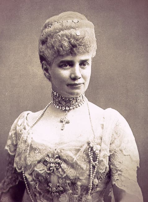 Thyra in an evening dress with a lace bertha and sleeves. She's wearing a diamond choker with a cross hanging from it.