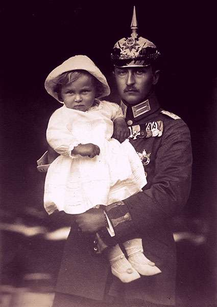 Prince August Wilhelm dressed in Prussian military uniform, holding his toddler son.